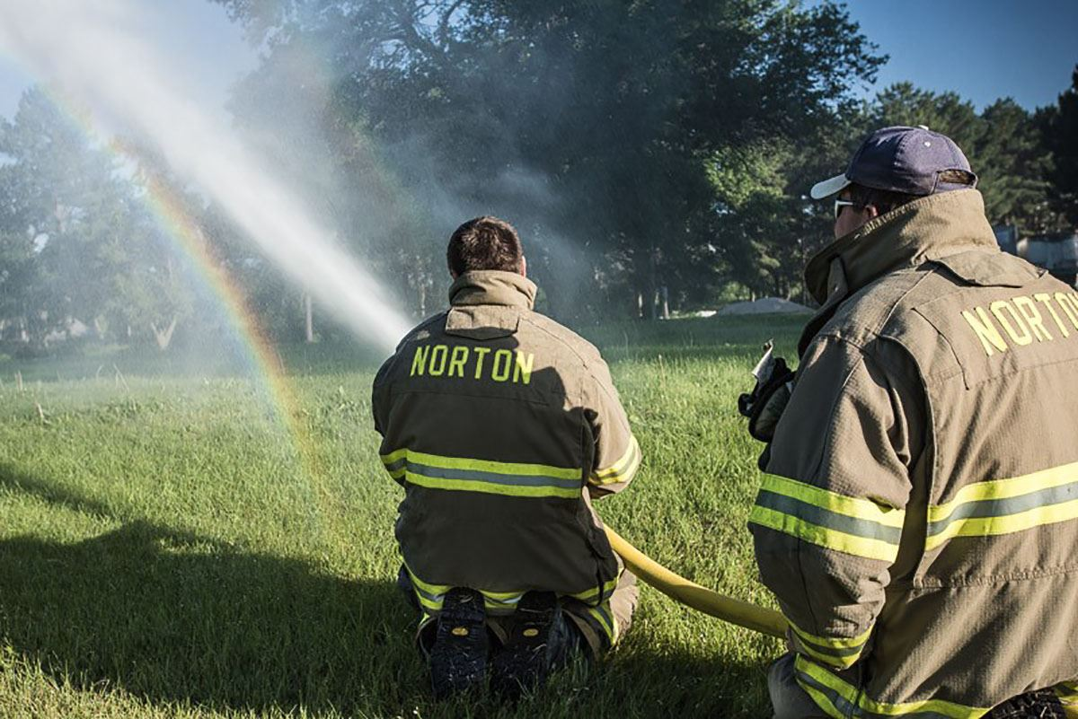 firemen spraying water out of fire hose onto grassy lawn